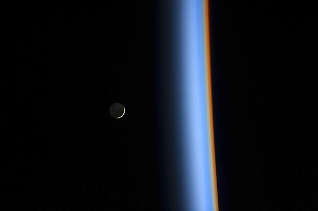 A crescent moon rises over the cusp of the Earth's atmosphere in this picture by Japan Aerospace Exploration Agency astronaut Koichi Wakata onboard the International Space Station taken February 1, 2014. REUTERS/NASA/Handout