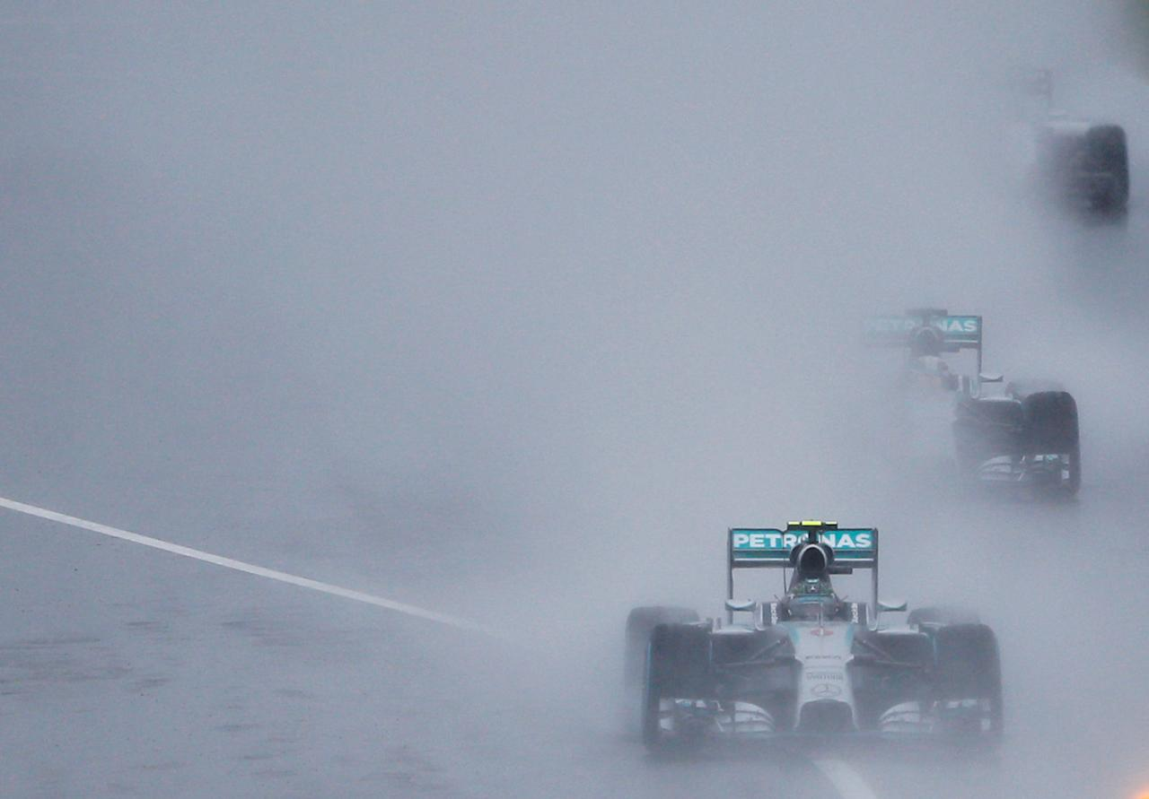 FILE PHOTO -  Mercedes Formula One driver Nico Rosberg (bottom) of Germany leads teammate Lewis Hamilton (C) of Britain and Williams Formula One driver Valtteri Bottas (top) of Finland behind a safety car (unseen) as they start the first lap of the rain-affected Japanese F1 Grand Prix at the Suzuka Circuit October 5, 2014.   REUTERS/Toru Hanai/File Photo