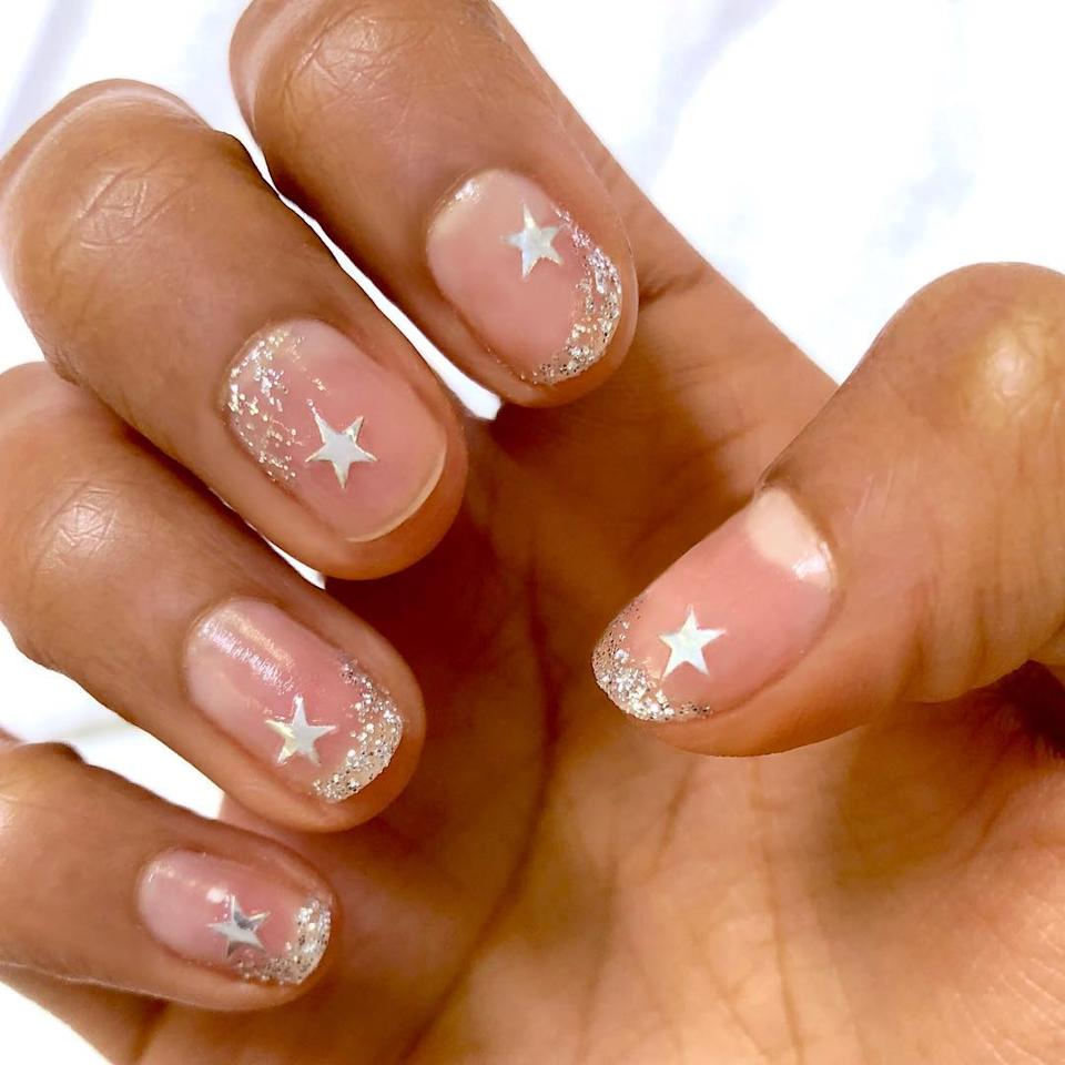 """Stick-on <a href=""""https://www.allure.com/story/star-nail-art-trend?mbid=synd_yahoo_rss"""">star nail art</a> was trending all summer, but it carries over beautifully into the winter, especially with the extra touch of glitter alternating between the tips and cuticles on otherwise bare nails, like in this <a href=""""https://www.instagram.com/p/BsEurg2BVqR/"""">Olive & June masterpiece</a>."""