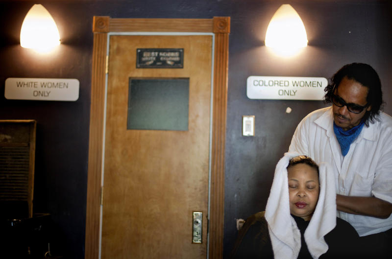 Ricci DeForest, right, curator of the Madame C.J. Walker Museum, an original beauty shop opened in 1950 by agents of the hair care entrepreneur who is considered the first self-made female American millionaire, washes the hair of Arletta Brinson Friday, June 8, 2012, in Atlanta's Auburn Avenue district. Today Auburn Avenue is a shell of its former self, the bustling mix of banks, night clubs, churches, meat markets and funeral homes long gone, replaced with crumbling facades and cracked sidewalks. Hundreds of thousands of people still flock to Auburn Avenue to see King's birth home, the church where he preached and the crypt where he and his wife, Coretta, are buried. But tourists have little reason to linger. While King's legacy has been preserved, Auburn Avenue's business community has never recovered from the exodus of the black community that supported it. This week, the area was placed on the National Register of Historic Places' 11 Most Endangered list for the second time since 1992 in hopes of spurring preservation-oriented development. (AP Photo/David Goldman)
