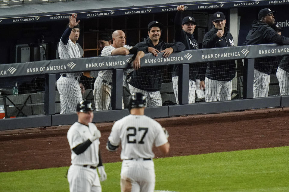 New York Yankees players gesture to Giancarlo Stanton (27) after stanton drove in a run with a single during the eighth inning of a baseball game against the Houston Astros Wednesday, May 5, 2021, in New York. The Yankees won 6-3. (AP Photo/Frank Franklin II)