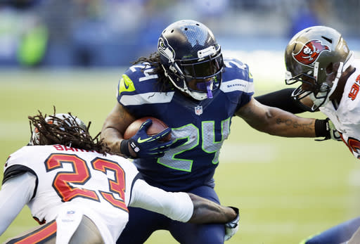 Seattle Seahawks running back Marshawn Lynch (24) runs through Tampa Bay Buccaneers' Mark Barron (23) and Tampa Bay Buccaneers' William Gholston in the second half of an NFL football game Sunday, Nov. 3, 2013, in Seattle. The Seahawks won 27-24 in overtime. (AP Photo/Stephen Brashear)