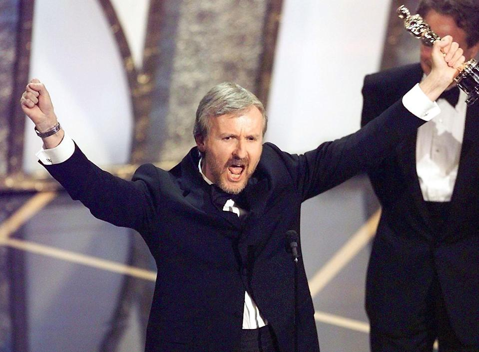 James Cameron raises his Oscar after winning Best Director for <em>Titanic</em> at the 70th Academy Awards. (Photo: Timothy A. Clary/AFP/Getty Images)