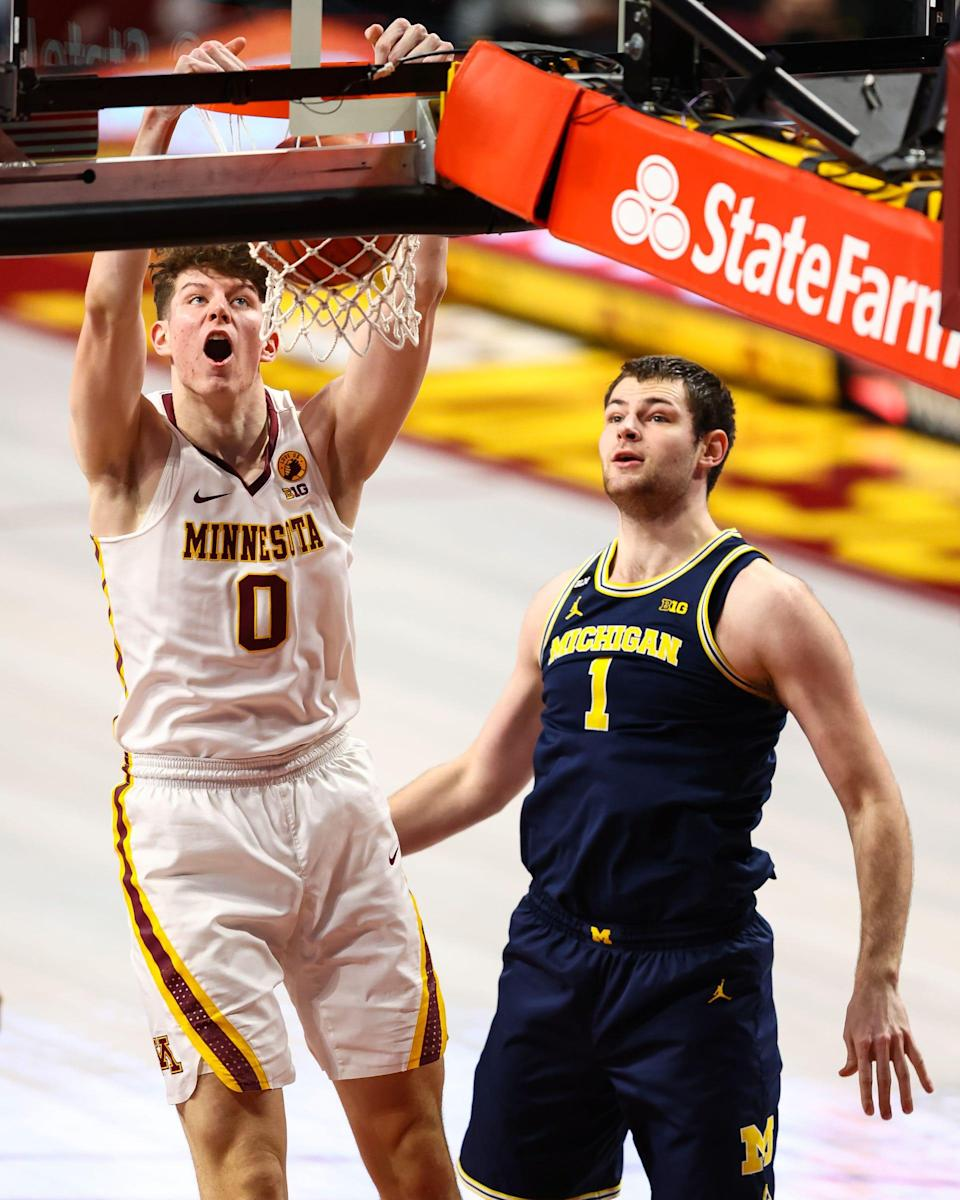 Minnesota center Liam Robbins dunks as Michigan Wolverines center Hunter Dickinson looks on during the first half at Williams Arena in Minneapolis, Jan. 16, 2021.