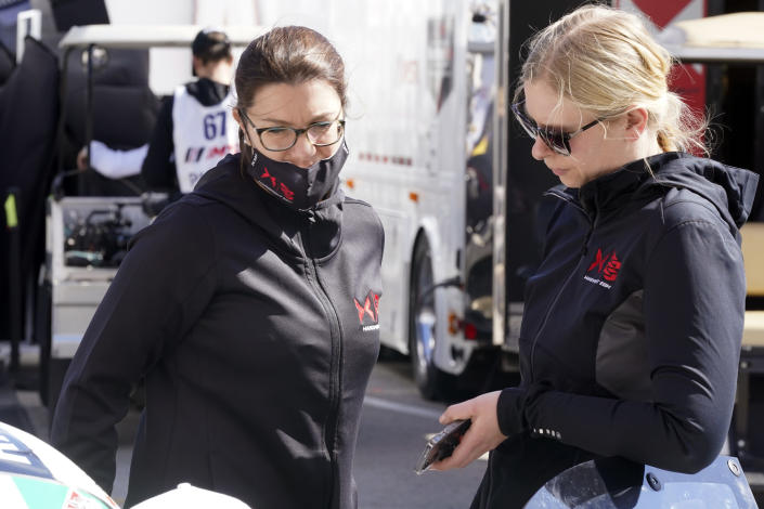 Drivers Katherine Legge, left, of Great Britain, and Christina Nielsen, of Denmark, talk outside their garage after a practice session for the Rolex 24 hour race at Daytona International Speedway, Friday, Jan. 29, 2021, in Daytona Beach, Fla. The two women will team up with drivers and team co-owners Rob Ferriol and Earl Bamber in the No. 88 Team Hardpoint EBM Porsche 911 GT3 R.(AP Photo/John Raoux)