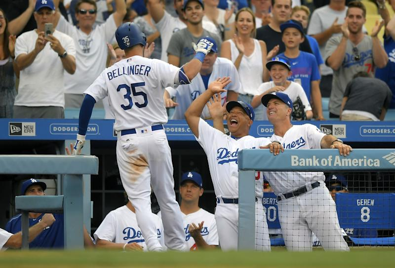 Los Angeles Dodgers' Cody Bellinger, left, is congratulated by manager Dave Roberts, center, and coach Bob Geren after hitting a solo home run during the eighth inning of a baseball game against the Kansas City Royals, Saturday, July 8, 2017, in Los Angeles.