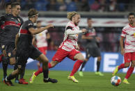 Leipzig's Emil Forsberg, center, on his way to scoring his sides second goal during the German Bundesliga soccer match between RB Leipzig and VfB Stuttgart in Leipzig, Germany, Friday, Aug. 20, 2021. (AP Photo/Michael Sohn)