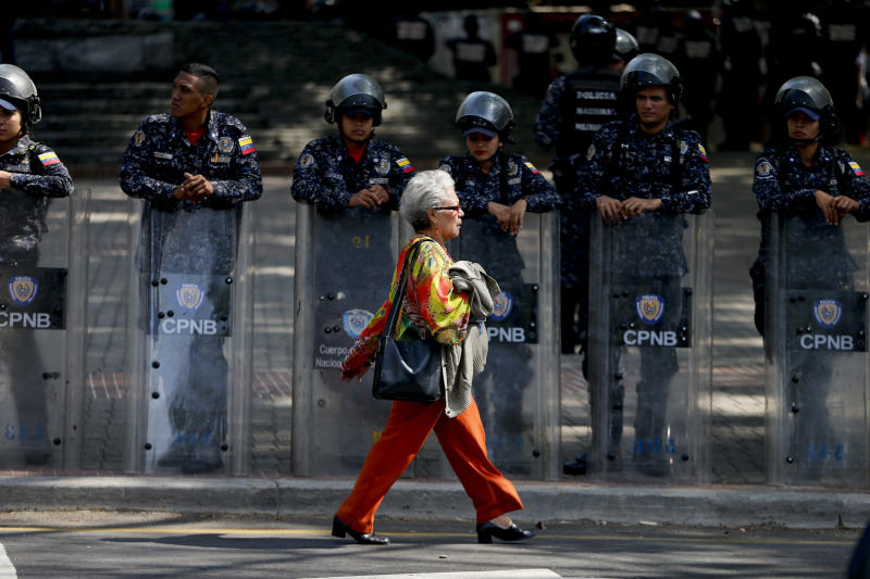 Police stand guard in anticipation of a march called by a coalition of opposition parties and civic groups who are petitioning lawmakers for a law of guarantees that will protect workers who have been victims of political retaliation and unjustified dismissals, in Caracas, Venezuela, Tuesday, March 19, 2019. (AP Photo/Natacha Pisarenko)