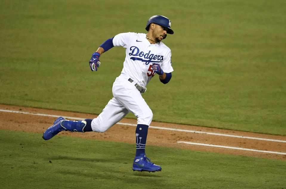 Mookie Betts #50 of the Los Angeles Dodgers rounds first on a two RBI double against the Milwaukee Brewers in the fifth inning of Game 2 of a National League wild-card baseball series MLB baseball game at Dodger Stadium in Los Angeles on Thursday, October 1, 2020. (Keith Birmingham/The Orange County Register via AP)