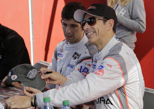 Acura Team Penske driver Helio Castroneves signs autographs before the Rolex 24 hour auto race at Daytona International Speedway, Saturday, Jan. 25, 2020, in Daytona Beach, Fla. (AP Photo/Terry Renna)