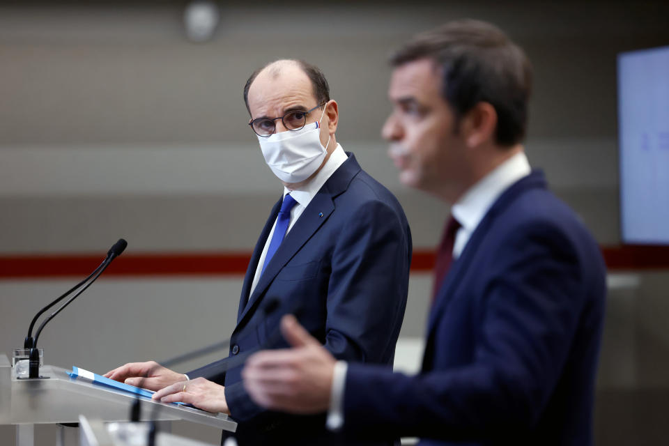 French Prime Minister Jean Castex, left, looks on as French Health Minister Olivier Veran speaks during a press conference in Paris, Thursday, Jan. 14, 2021. Trying to fend off the need for a third nationwide lockdown that would further dent Europe's second-largest economy and endanger more jobs, France is instead opting for creeping curfews. The prime minister announced Thursday an extension of the 6 p.m.-to-6 a.m. curfew to cover the whole country. (Thomas Coex, Pool Photo via AP)