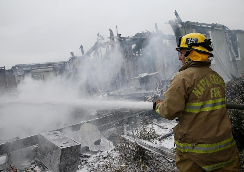 A Napa County firefighter sprays foam on hot spots from a fire at a mobile home park following a reported 6.0 earthquake on August 24, 2014 in Napa, California (AFP Photo/Justin Sullivan)