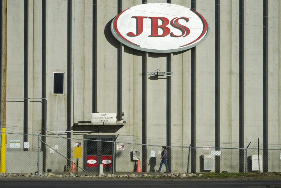 FILE - In this Oct. 12, 2020 file photo, a worker heads into the JBS meatpacking plant in Greeley, Colo. The world's largest meat processing company says it paid the equivalent of $11 million to hackers who broke into its computer system late last month. Brazil-based JBS SA said on May 31 that it was the victim of a ransomware attack, but Wednesday, June 9, 2021 was the first time the company's U.S. division confirmed that it had paid the ransom. (AP Photo/David Zalubowski, File)