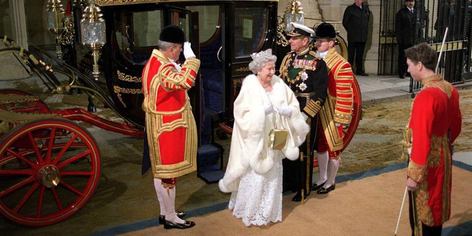 <p> The queen wore a cream coat with fur trim, a white gown, a tiara, and a gold purse for a state opening of Parliament.</p>