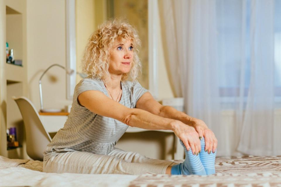 middle age white woman stretches on bed by holding onto her feet