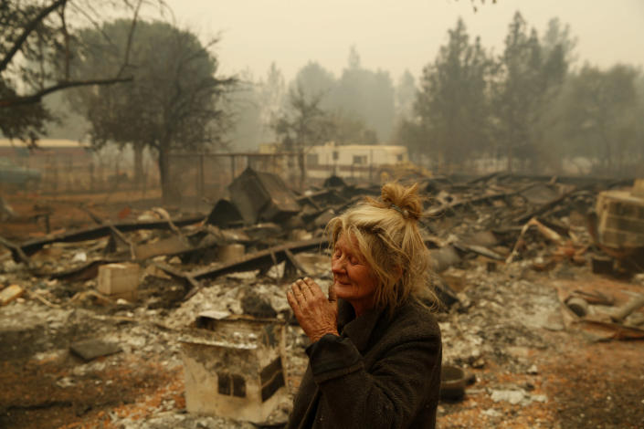 """<p>Cathy Fallon reacts as she stands near the charred remains of her home on Nov. 9, 2018, in Paradise, Calif. """"I'll be darned if I'm going to let those horses burn in the fire,"""" said Fallon, who stayed on her property to protect her 14 horses, all of which survived. (Photo: John Locher/AP) </p>"""