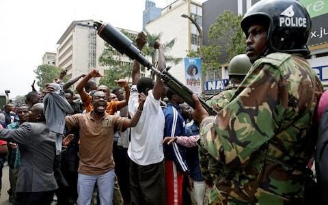 Police watch the cheering crowd outside the court in Nairobi - Credit: BAZ RATNER/Reuters