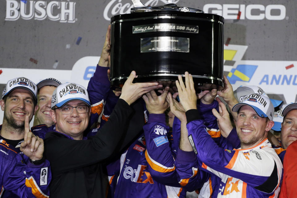 Denny Hamlin, right, celebrates as he and crew members hoist the championship trophy after winning the NASCAR Daytona 500 auto race at Daytona International Speedway, Monday, Feb. 17, 2020, in Daytona Beach, Fla. (AP Photo/Terry Renna)