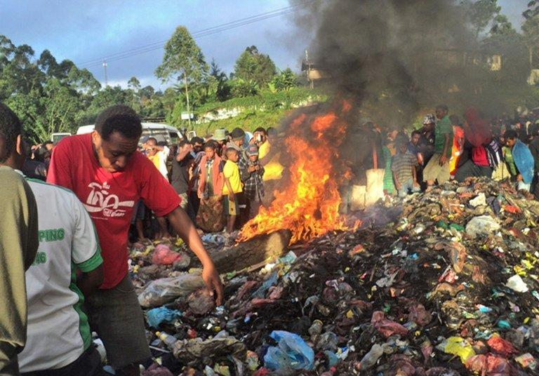This photo, taken on February 6, 2013, shows a young mother accused of sorcery who was stripped naked, reportedly tortured with a branding iron, tied up, splashed with fuel and set alight on a pile of rubbish topped with car tyres, in Mount Hagen city in the Western Highlands of Papua New Guinea. She was torched by villagers who claimed she killed a six-year-old boy through sorcery
