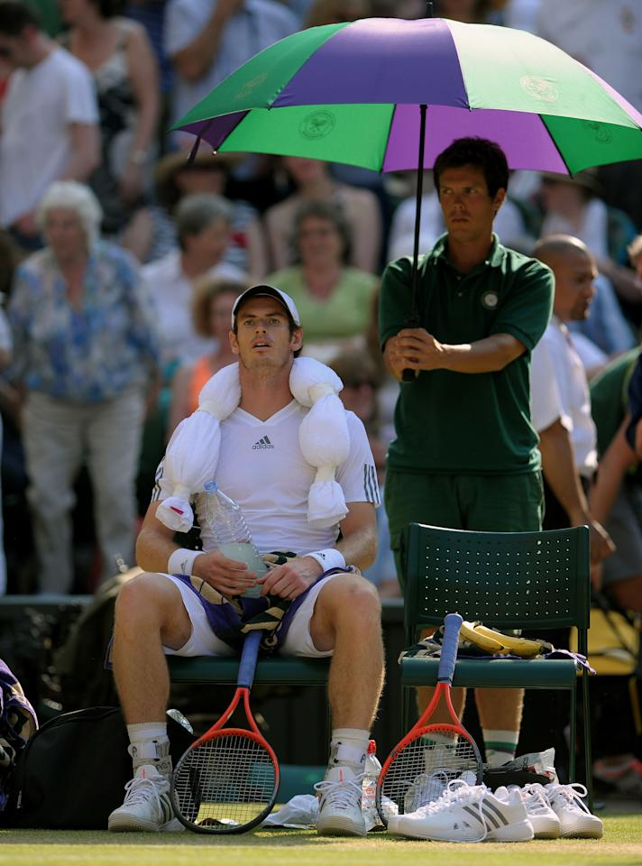 Great Britain's Andy Murray sits with a towel of ice on his head during a break of ends in his match against Serbia's Novak Djokovic on day thirteen of the Wimbledon Championships at The All England Lawn Tennis and Croquet Club, Wimbledon.