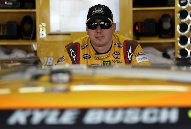 Driver Kyle Busch leans on his car as he waits during practice for Sunday's running of the NASCAR Sprint Cup Series auto race at Talladega Superspeedway in Talladega, Ala., Friday, Oct. 18, 2013
