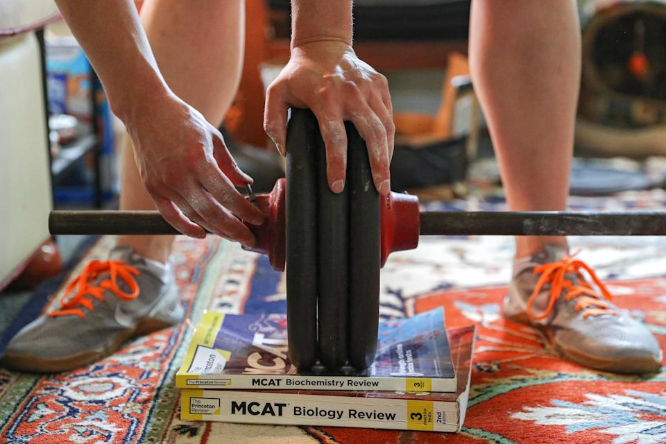 PRINCETON, NEW JERSEY - MAY 28: Medical College Admission books owned by U.S. Olympic fencer Katharine Holmes support her weights as she trains at her home on May 28, 2020 in Princeton, New Jersey. An Olympian, World Championship gold medalist and Pan American gold medalist - she continues to focus on winning gold at the Tokyo 2020 Olympics - which have been postponed to 2021 due the coronavirus. The epee fencer was training anywhere from 6-8 hours a day at Princeton University before the Covid-19 pandemic, but now continues that intense regime at home. Athletes across the globe are now training in isolation under strict policies in place due to the Covid-19 pandemic. (Photo by Patrick Smith/Getty Images)