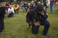 Members of the Proud Boys and other right-wing demonstrators kneel in prayer at rally on Saturday, Sept. 26, 2020, in Portland, Ore. (AP Photo/Allison Dinner)