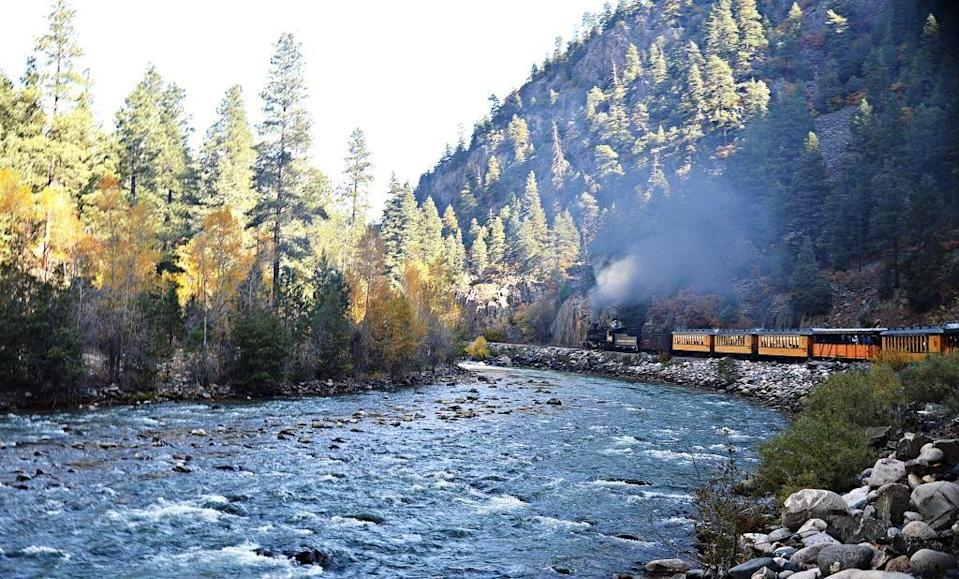"""<p>Originally opened to transport gold and silver ore mined from Colorado's San Juan Mountains, the <a href=""""https://www.durangotrain.com/"""" rel=""""nofollow noopener"""" target=""""_blank"""" data-ylk=""""slk:Durango and Silverton Narrow Gauge Railroad"""" class=""""link rapid-noclick-resp"""">Durango and Silverton Narrow Gauge Railroad</a> is now a popular historic railway with """"unparalleled scenery,"""" as its website describes. The train has been in continuous operation since 1882. Passengers can expect views of the Animas river (pictured here), the iconic Horseshoe Curve, and the High Bridge. </p>"""
