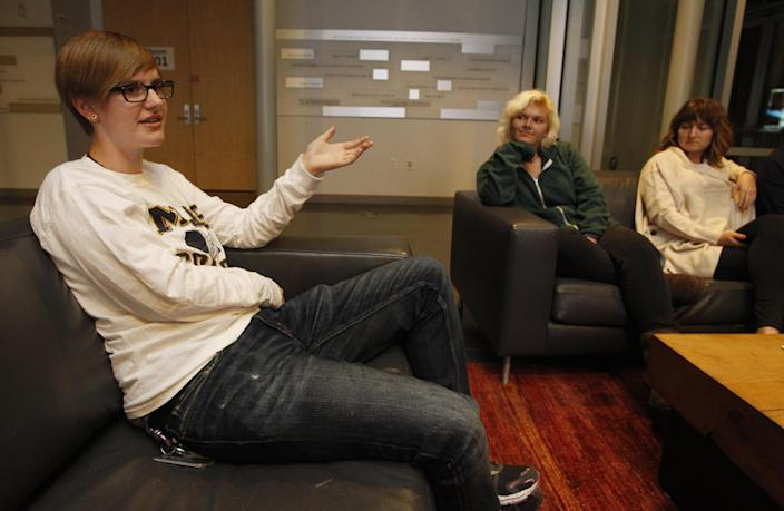 """Skylar Crownover, left, discusses preferred gender pronouns with Joss Ferguson, center, Maria McCann and other members of Mouthing Off!, an LGBT student group at Mills College in Oakland, Calif., on Monday, Nov. 25, 2013. """"Because I go to an all-women's college, a lot of people are like, 'If you don't identify as a woman, how did you get in?'"""" said Crownover, 19, who is president of Mouthing Off! and prefers to be mentioned as a singular they, but also answers to he. """"I just tell them the application asks you to mark your sex and I did. It didn't ask me for my gender."""" (AP Photo/Mathew Sumner)"""