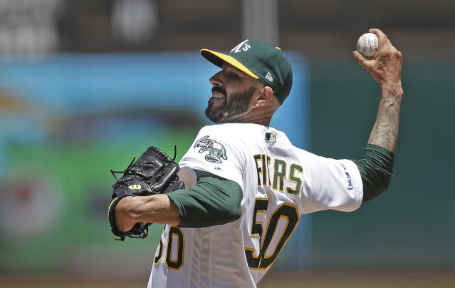 FILE - In this May 25, 2019, file photo, Oakland Athletics pitcher Mike Fiers works against the Seattle Mariners in the first inning of a baseball game in Oakland, Calif. Fiers and the Athletics might have reason to be downright mad. They won 97 games each of the past two seasons to finish as the second-place team in the AL West behind the Houston Astros, whom Fiers called out in November in a story by The Athletic for a sign-stealing scheme that led to season-long MLB suspensions for Astros general manager Jeff Luhnow and manager AJ Hinch. Fiers insisted at Fan Fest that he is moving forward, declining to address anything regarding what he did by speaking out or even his role cleaning up the sport. He said he owes that to his teammates. (AP Photo/Ben Margot, File)