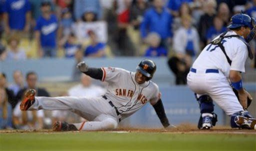 San Francisco Giants' Joaquin Arias, left, scores on a double by Andres Torres as Los Angeles Dodgers catcher A.J. Ellis takes a late throw during the second inning of their baseball game, Monday, June 24, 2013, in Los Angeles. (AP Photo/Mark J. Terrill)