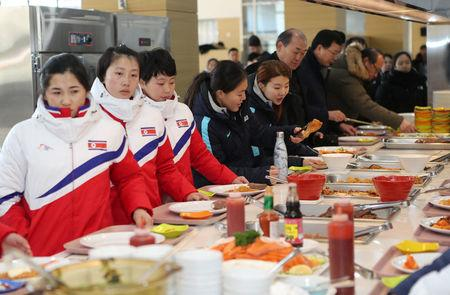 North and South Korea women's ice hockey athletes stand in a line at a dining hall at the Jincheon National Training Centre in Jincheon