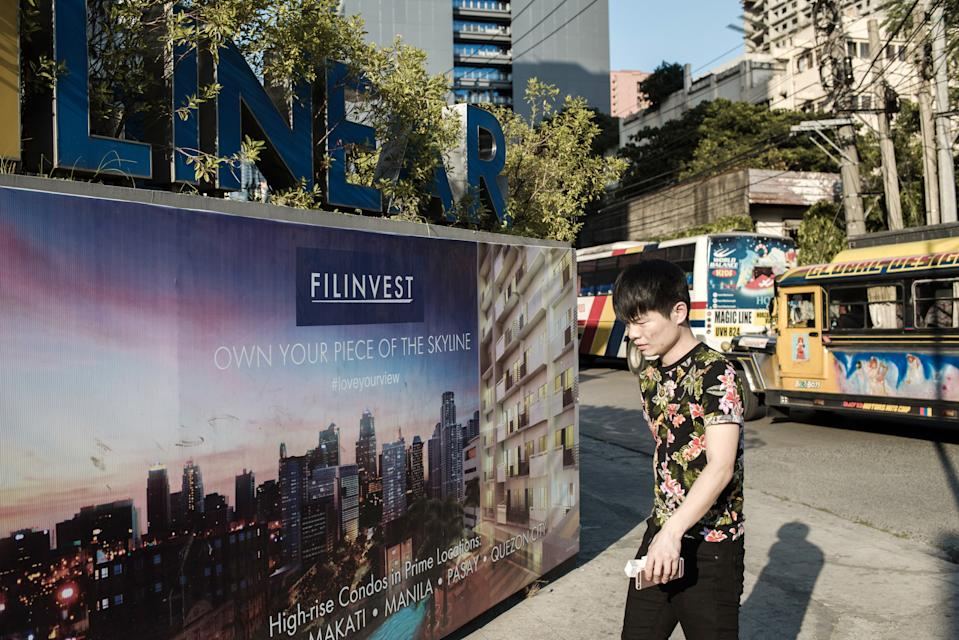 FILE PHOTO: A pedestrian walks past signage for Filinvest.com advertising property investment outside The Linear Makati development in the San Antonio Village area of Makati City, Manila, the Philippines, May 2, 2018. (Photo: Carlo Gauco/Bloomberg)