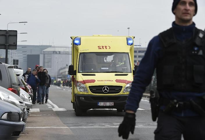 A Belgian emergency vehicle drives past passengers evacuating the Brussels Airport on March 22, 2016, after a string of explosions (AFP Photo/John Thys)