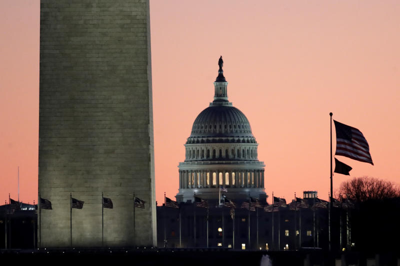 The U.S. Capitol building, center, is seen next to the bottom part of the Washington Monument, left, before sunrise on Capitol Hill in Washington, Thursday, Dec. 19, 2019, a day after the U.S. House voted to impeach President Donald Trump on two charges, abuse of power and obstructing Congress. (AP Photo/Julio Cortez)