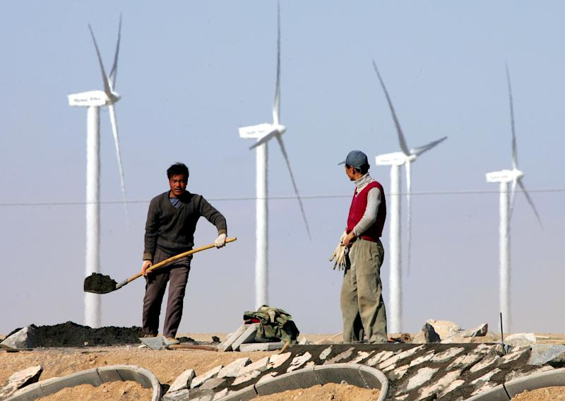 ** FILE ** In this Oct. 12, 2005 file photo, workers build a highway near a wind farm in the Gobi desert, in China's northwest Gansu province. Global investments in renewable energy jumped by 32 percent to $211 billion last year, boosted by wind farm development in China and rooftop solar panels in Europe, U.N. officials said Thursday July 7 2011.  A report by the U.N. Environment Program shows that solar, wind, biomass and other forms of green energy are gaining momentum, despite the lack of progress in international climate talks aimed at slowing emissions of heat-trapping gases from fossil fuels. (AP Photo/Greg Baker, File)