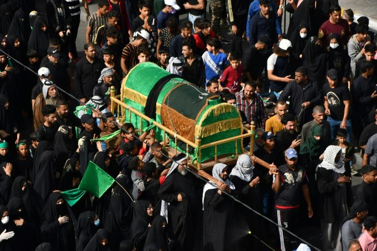 Shiites in the southern Iraqi city of Nasiriyah, unable to reach the mausouleum of Imam al-Kadhim in Baghdad, parade a mock coffin to commemorate his death
