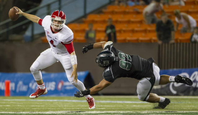 Fresno State quarterback Derek Carr (4) manages to escape from Hawaii defensive lineman Beau Yap (92) in the fourth quarter of an NCAA college football game Saturday, Sept. 28, 2013, in Honolulu. Fresno State defeated Hawaii 42-37. (AP Photo/Eugene Tanner)