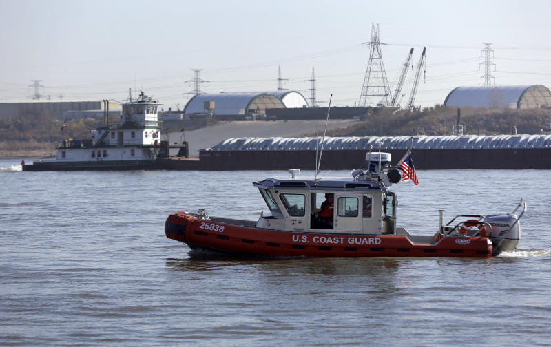 A Coast Guard boat patrols in the foreground as a barge makes its way down the Mississippi River Friday, Nov. 16, 2012, in St. Louis. A top Corps of Engineers official has ordered the release of water from an upper Mississippi River reservoir in an effort to avoid closure of the river at St. Louis to barge traffic due to low water levels caused by drought. (AP Photo/Jeff Roberson)