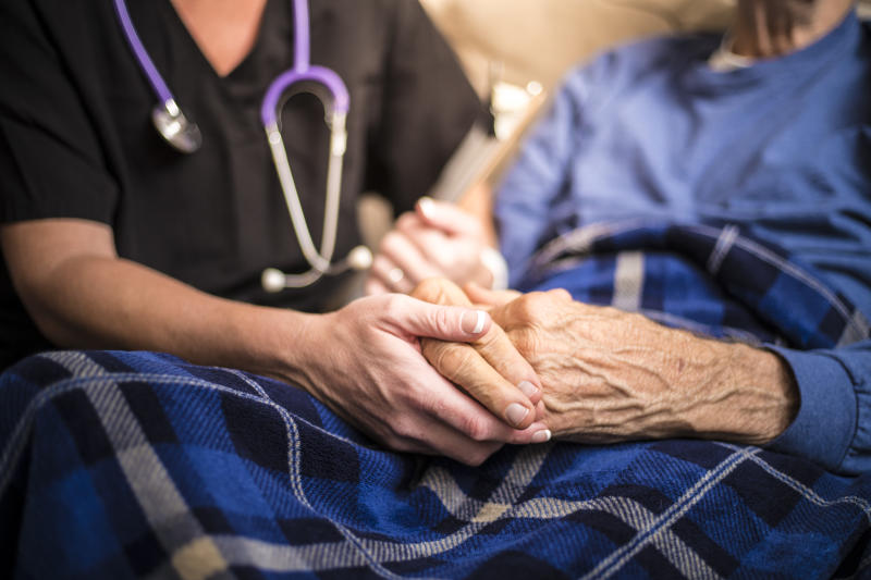 A stock photo of a Hospice Nurse visiting an Elderly male patient who is receiving hospice/palliative care.