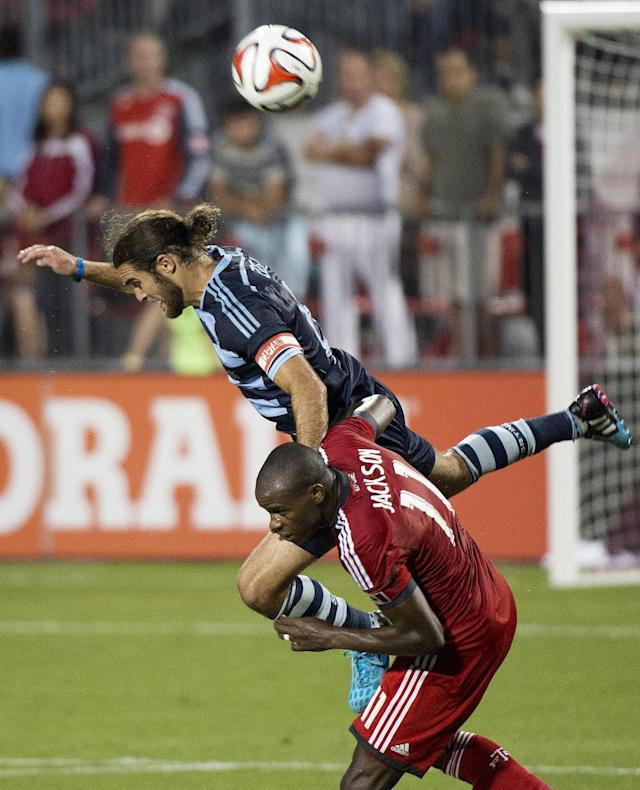 Toronto FC midfielder Jackson, bottom, battles for the ball against Sporting Kansas City's Graham Zusi, top, during second-half MLS soccer game action in Toronto, Saturday, July 26, 2014. (AP Photo/The Canadian Press, Nathan Denette)