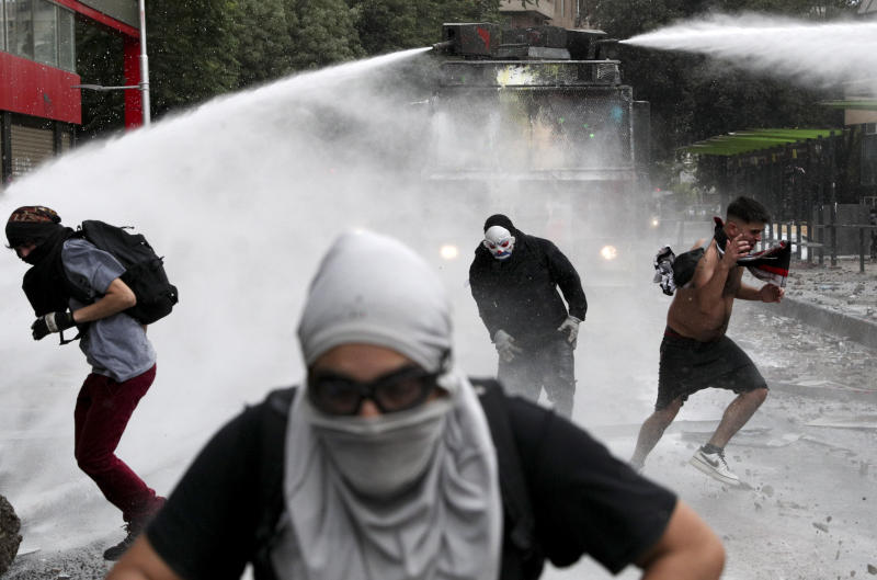 Anti-government protesters run from an advancing police water cannon in Santiago, Chile, Friday, Nov. 8, 2019. Chile's president on Thursday announced measures to increase security and toughen sanctions for vandalism following three weeks of protests that have left at least 20 dead. (AP Photo/Esteban Felix)