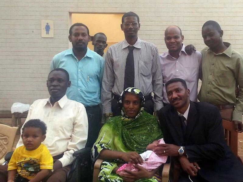 Meriam Yahia Ibrahim Ishag (C), a Christian Sudanese woman sentenced to hang for apostasy, is seen with her husband (L), her newborn baby and 20-month-old son and members of the legal team in Khartoum on June 23, 2014 (AFP Photo/)