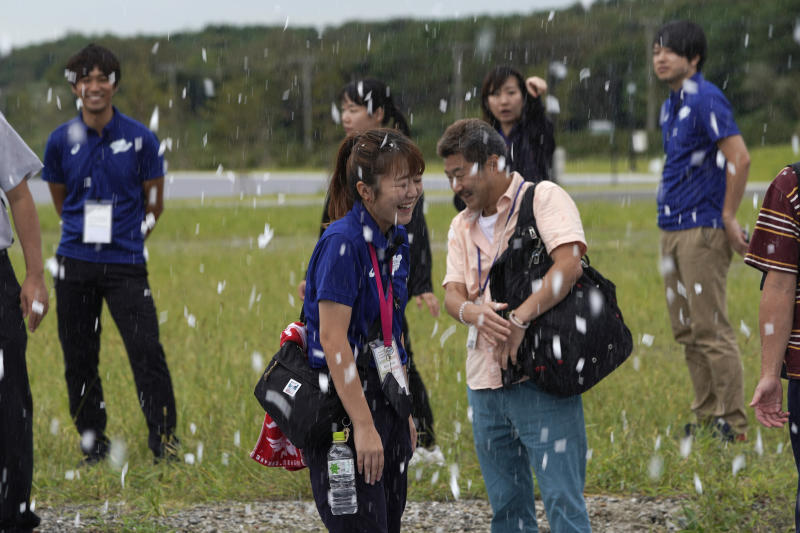 TOKYO, JAPAN - SEPTEMBER 13: Officials react to sprayed artificial snow from snow-making machines to ease heat during a canoe sprint test event for the Tokyo 2020 Olympic and Paralympic Games at Sea Forest Waterway, on September 13, 2019 in Tokyo, Japan. (Photo by Toru Hanai/Getty Images)