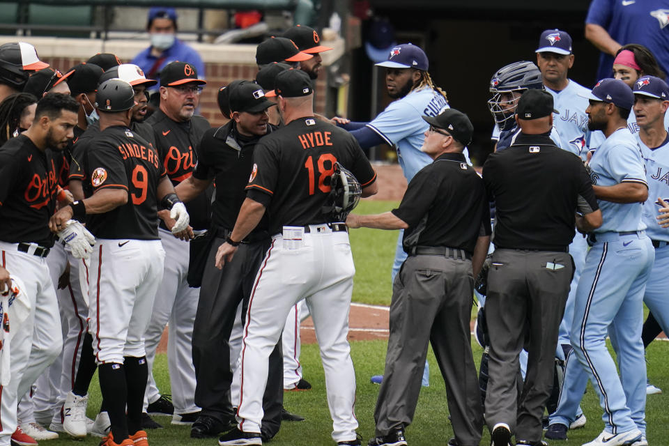 Baltimore Orioles manager Brandon Hyde (18) talks with home plate umpire Roberto Ortiz, center left, as members of the Orioles and Toronto Blue Jays engage in a benches-clearing argument after Blue Jays' Alek Manoah hit Orioles' Maikel Franco with a pitch during the fourth inning of a baseball game, Saturday, June 19, 2021, in Baltimore. The hit by a pitch came after Manoah gave up back-to-back home runs to Orioles' Ryan Mountcastle and DJ Stewart, which prompted the argument. (AP Photo/Julio Cortez)