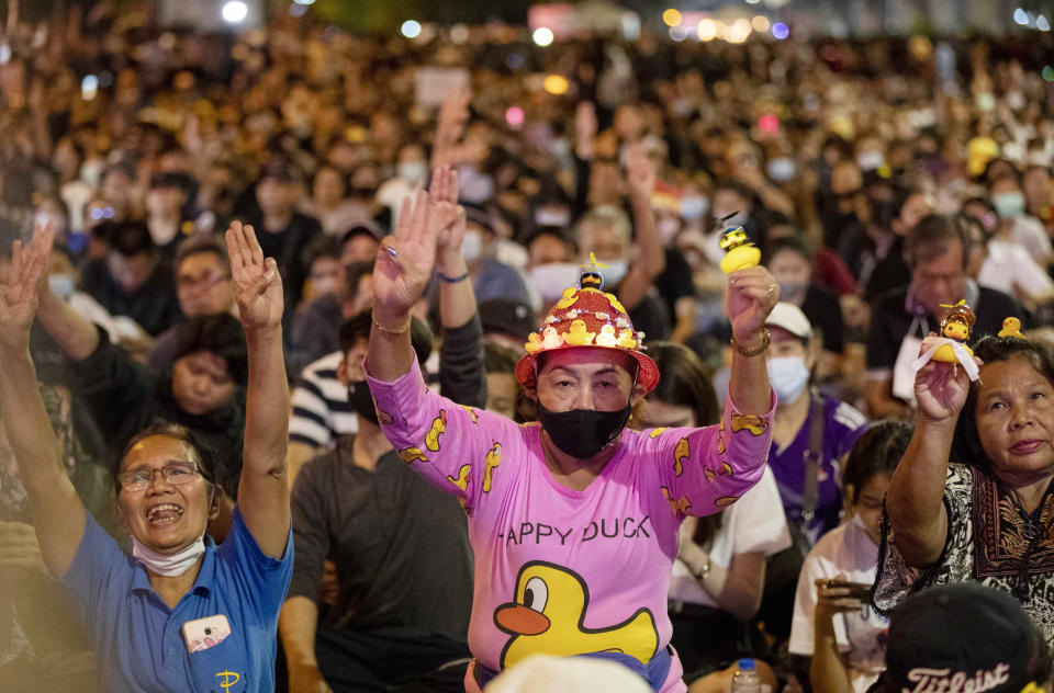 Anti-government protesters flash the three finger protest gesture during a rally Wednesday, Dec. 2, 2020 in Bangkok, Thailand. Thailand's highest court Wednesday acquitted Prime Minister Prayuth Chan-ocha of breaching ethics clauses in the country's constitution, allowing him to stay in his job. (AP Photo/Gemunu Amarasinghe)