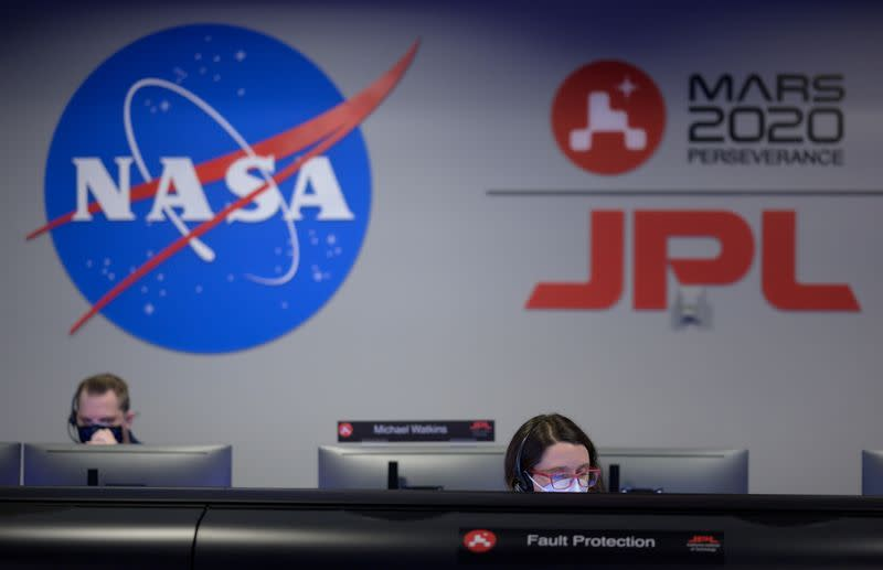 Members of NASA's Perseverance Mars rover team study data on monitors in mission control at NASA's Jet Propulsion Laboratory