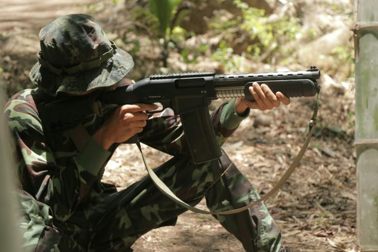 An anti-coup activist in Myanmar aims a weapon while undergoing basic military training at a camp of the Karen National Union
