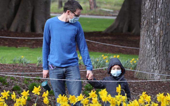 A man and a child, both wearing a face mask, walk at Fitzroy Gardens in East Melbourne, Victoria - DAVID CROSLING/EPA-EFE/Shutterstock