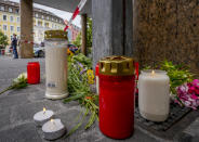 Flowers and candles were laid at the crime scene in central Wuerzburg, Germany, Saturday, June 26, 2021. German police say several people have been killed and others injured in a knife attack in the southern city of Wuerzburg on Friday. (AP Photo/Michael Probst)